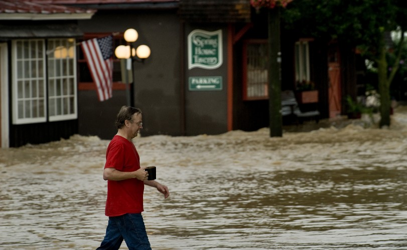 Mark Tye carries a cup of coffee as he walks across flooded Main Street from his apartment  on Monday morning.  Rich Cooley/Daily